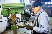 Senior Farmer Man Using Drill Press in Workshop