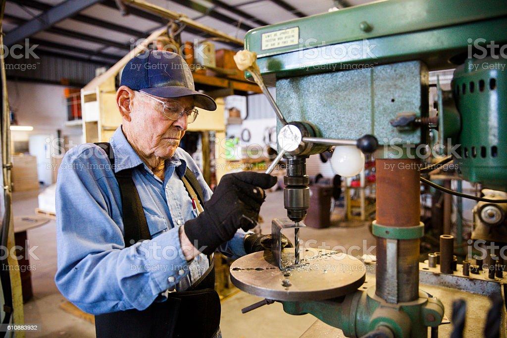 Senior Farmer Man Using Drill Press in Workshop stock photo