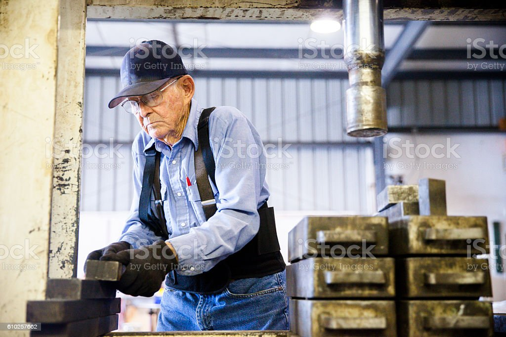 Senior Farmer Operating Hydraulic Press stock photo