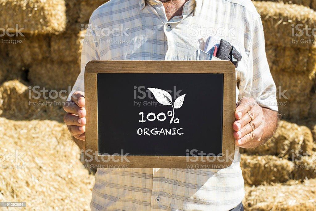 Senior Farmer Showing Organic Sign 100% stock photo