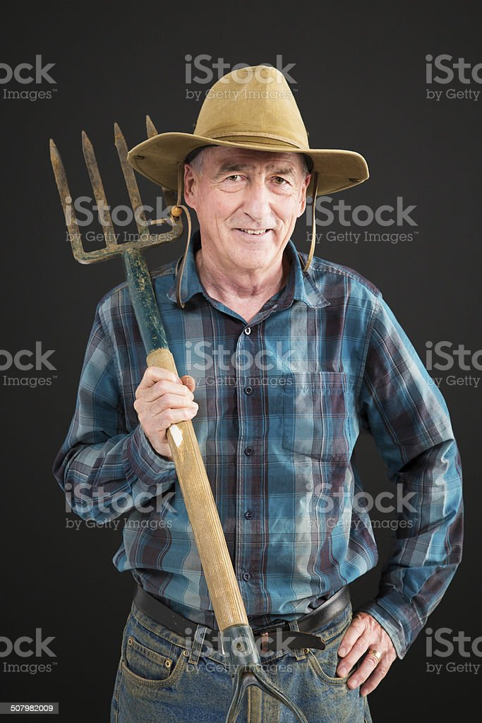 Senior farmer with pitch fork stock photo