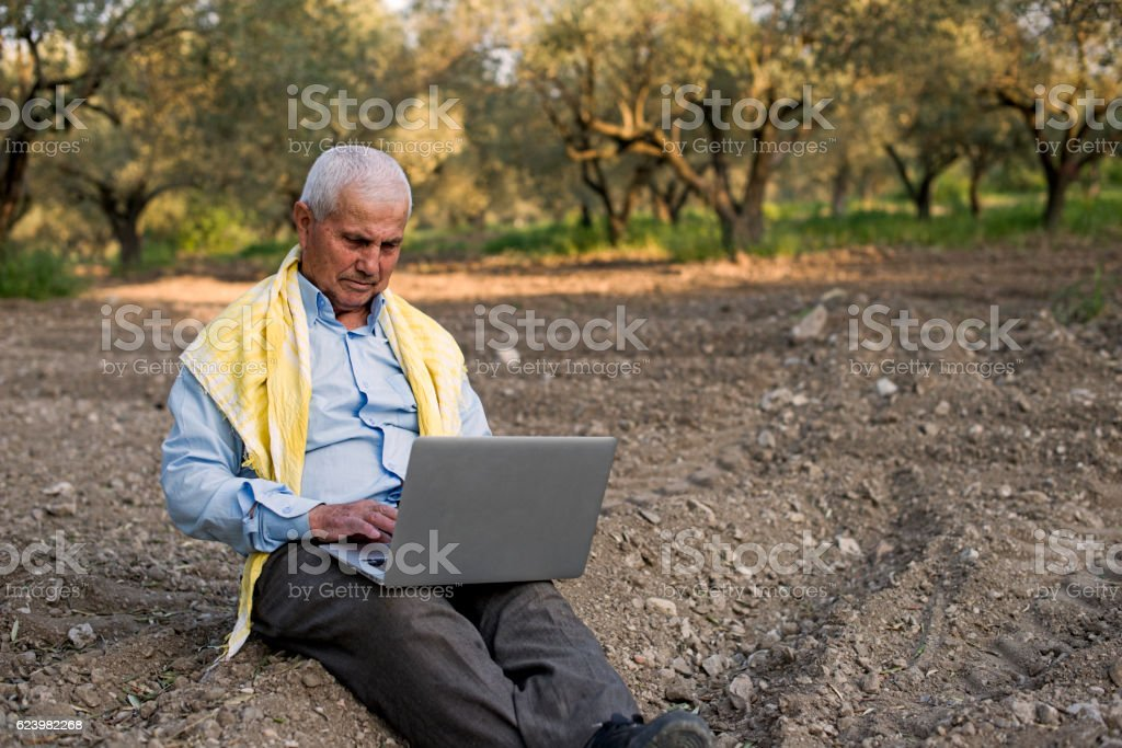 Senior Farmer With Their Laptop in The Field stock photo