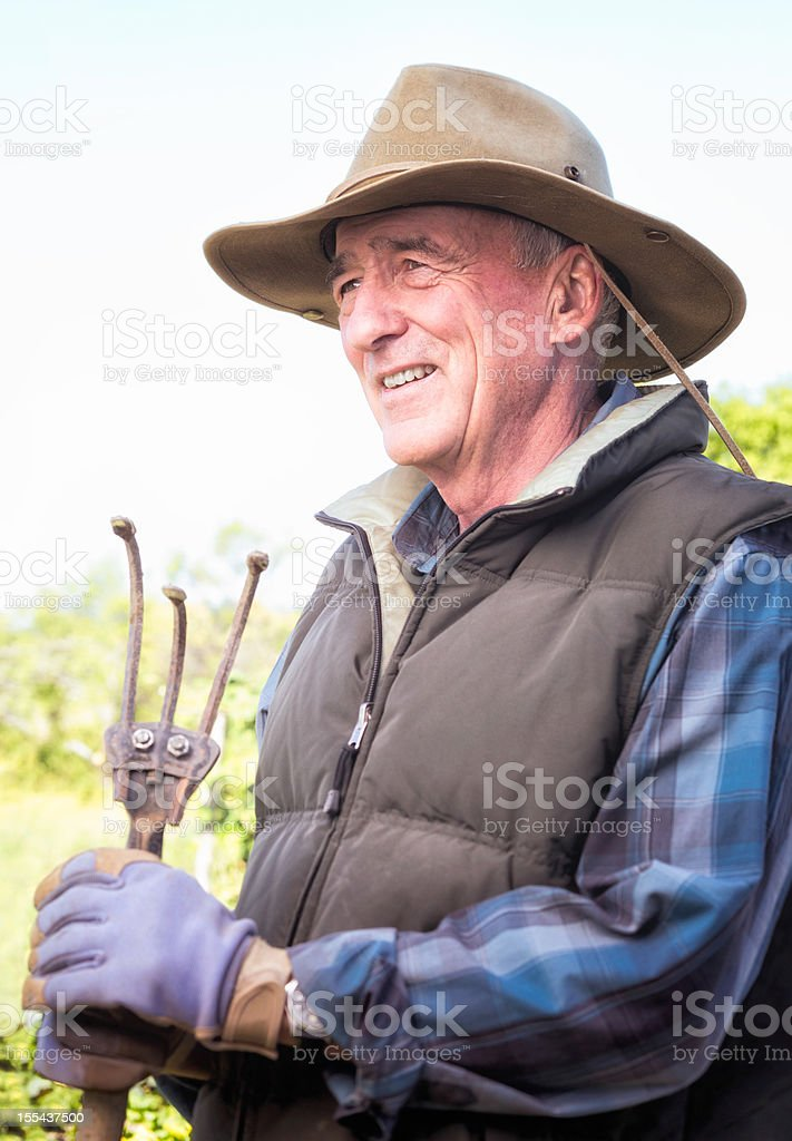 Senior farmer with weeding hoe looking left royalty-free stock photo