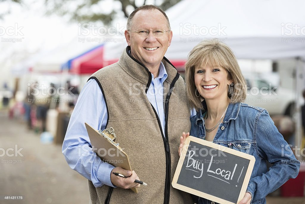 Senior farmers market managers holding buy local chalkboard sign stock photo