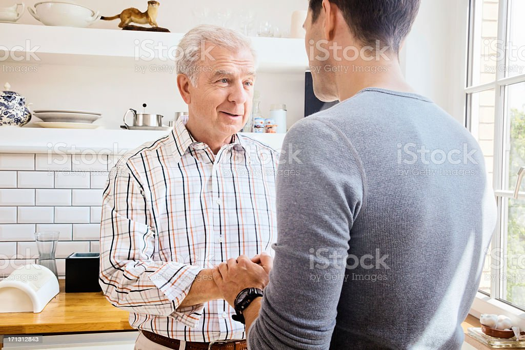 Senior father sharing good news with adult son in Kitchen royalty-free stock photo