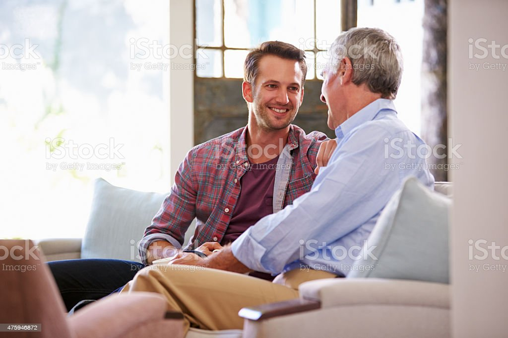Senior Father With Adult Son Relaxing On Sofa At Home stock photo
