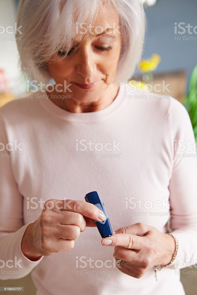 Senior Female Diabetic Checking Blood Sugar Levels stock photo