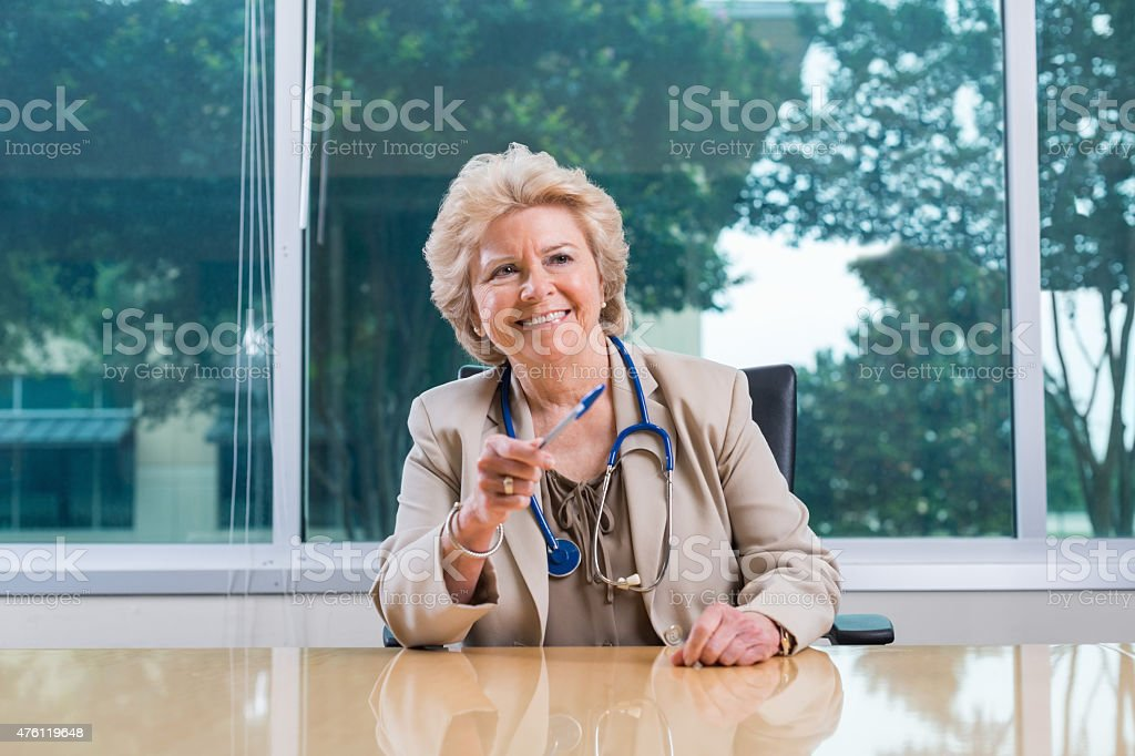 Senior female doctor seated at head of board table stock photo