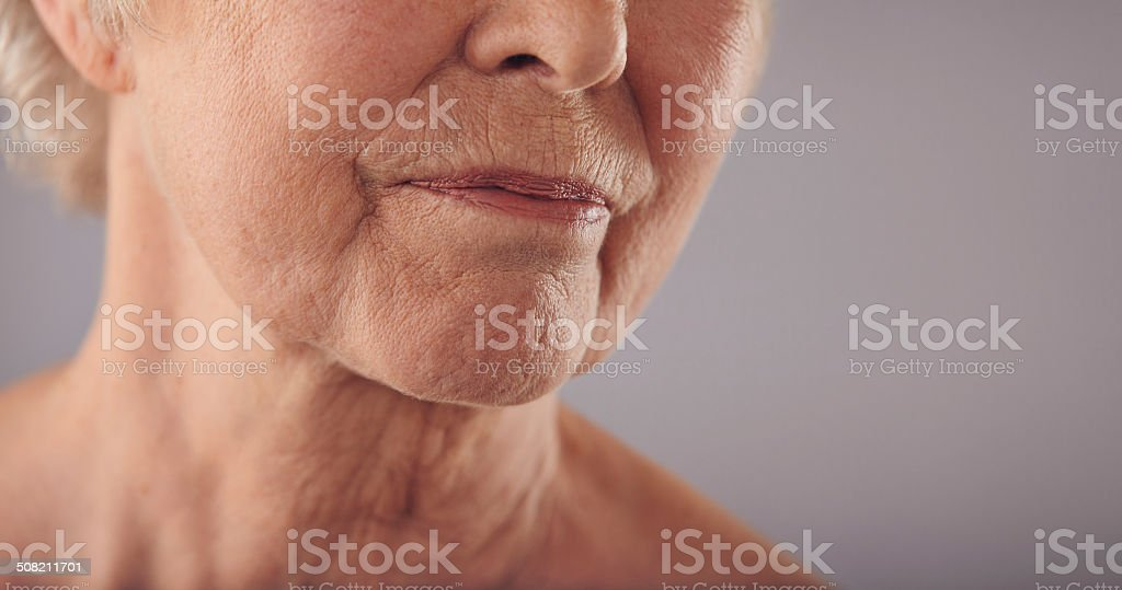 Senior female face with wrinkled skin stock photo