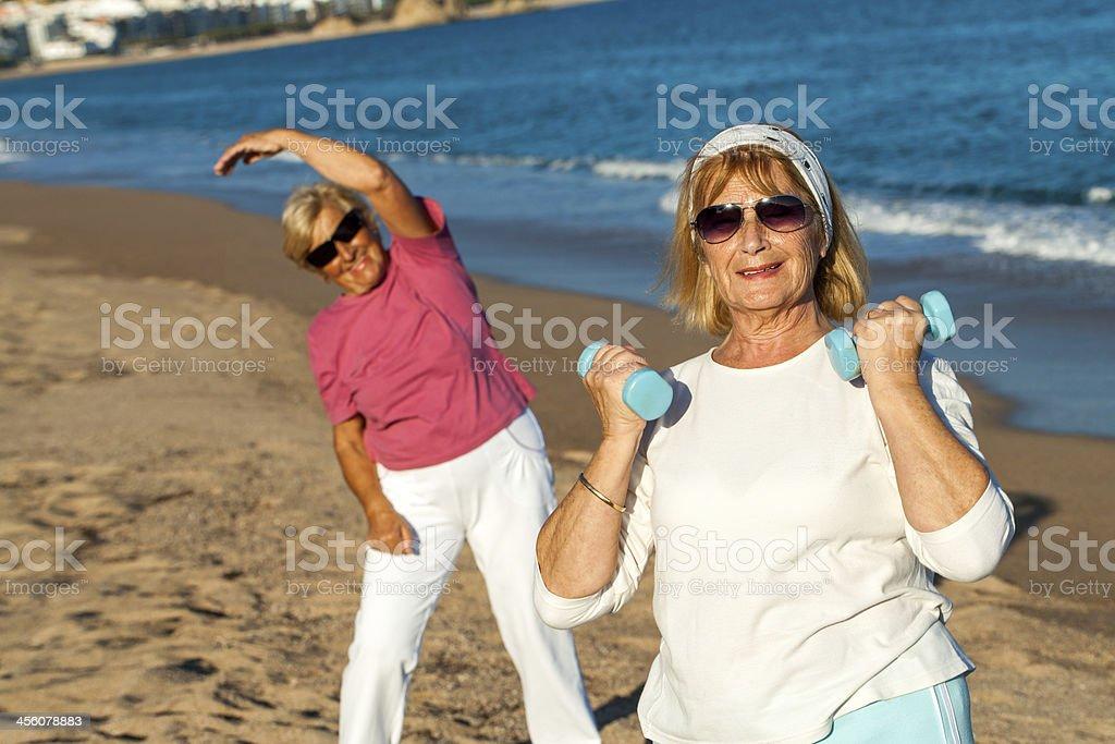 Senior femme séance de remise en forme sur la plage. photo libre de droits