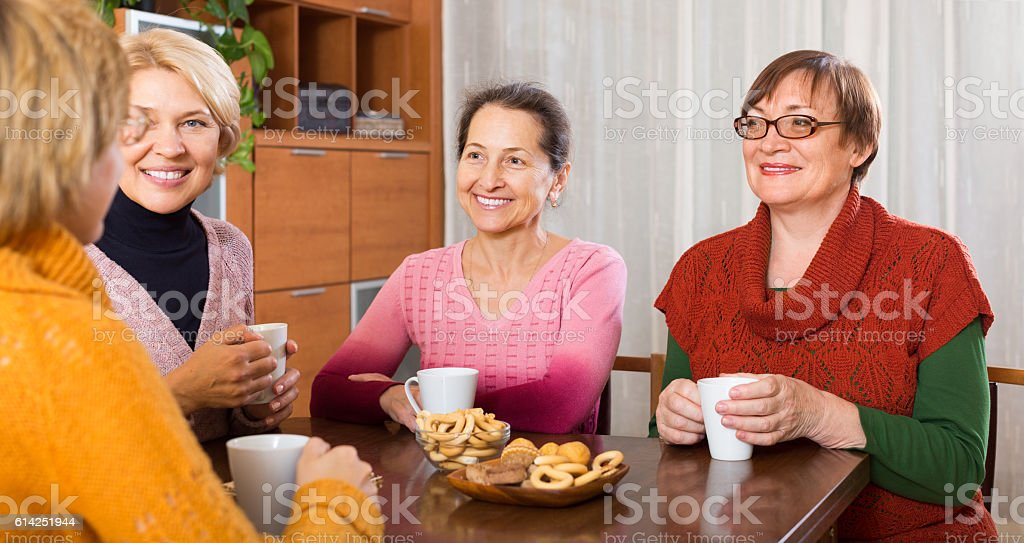 Senior female friends drinking coffee stock photo