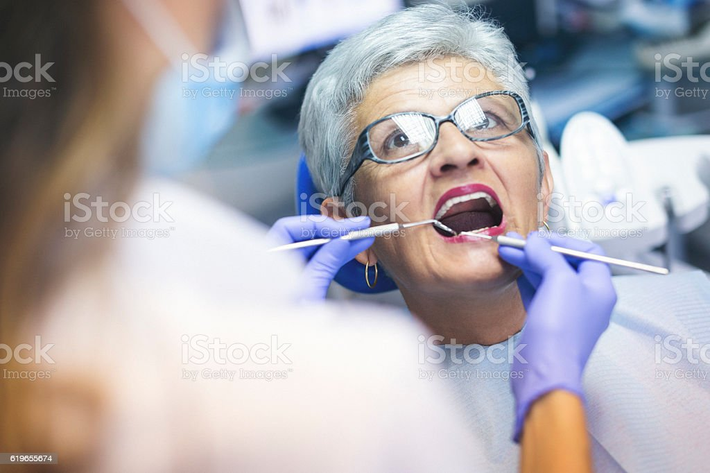 Senior female patient at dentist office stock photo