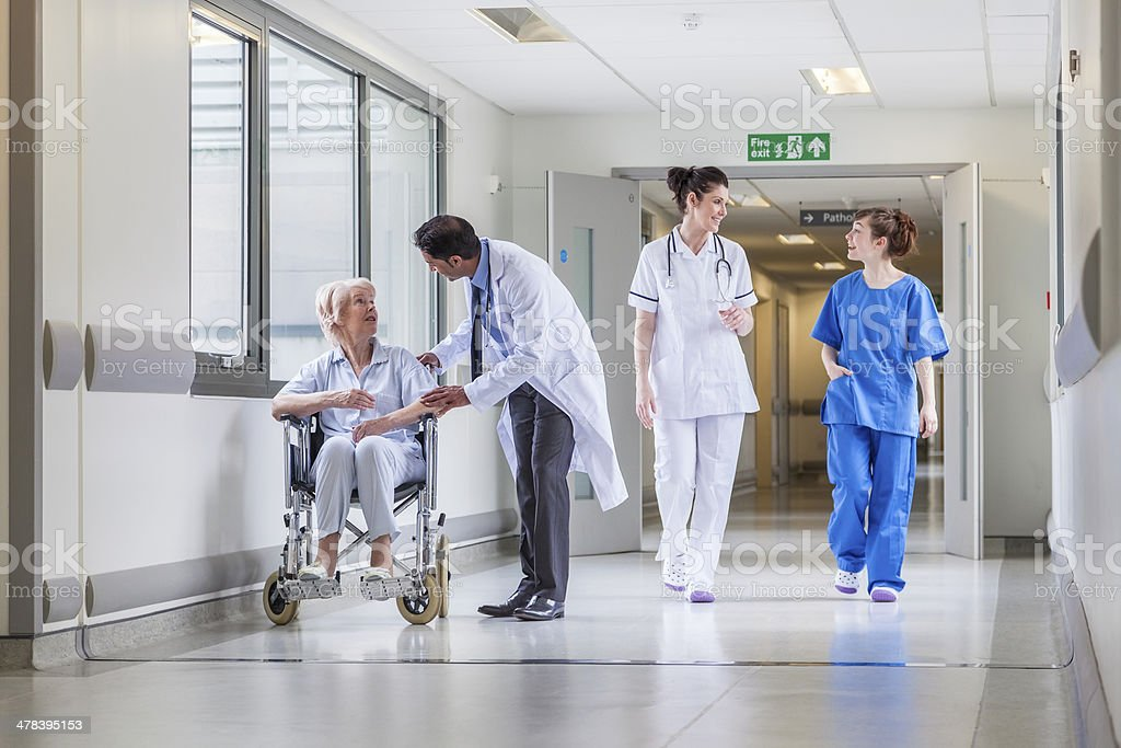 Senior Female Patient in Wheelchair & Doctor in Hospital stock photo