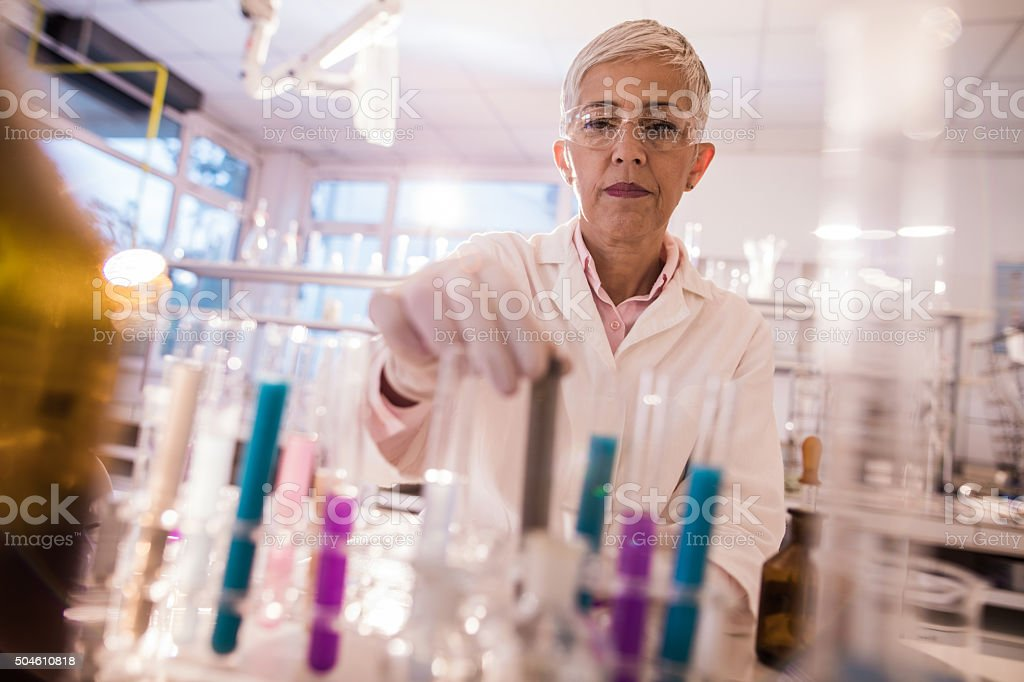 Senior female scientist taking a test tube with toxic substance. stock photo