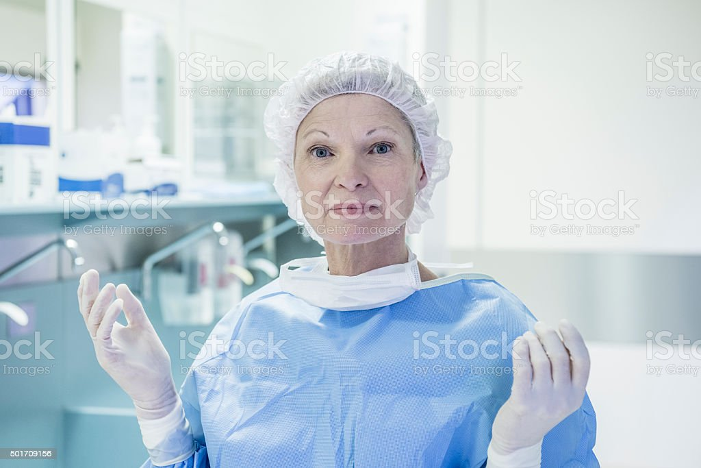 Senior female surgeon wearing surgical cap and latex gloves stock photo