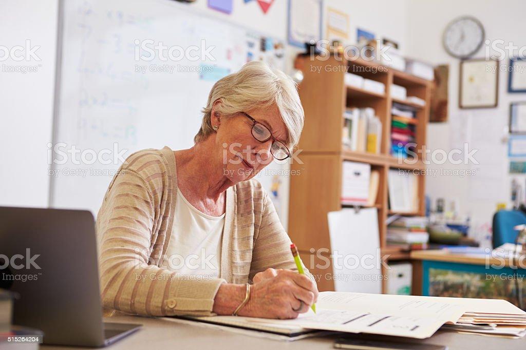 Senior female teacher at her desk marking students' work stock photo