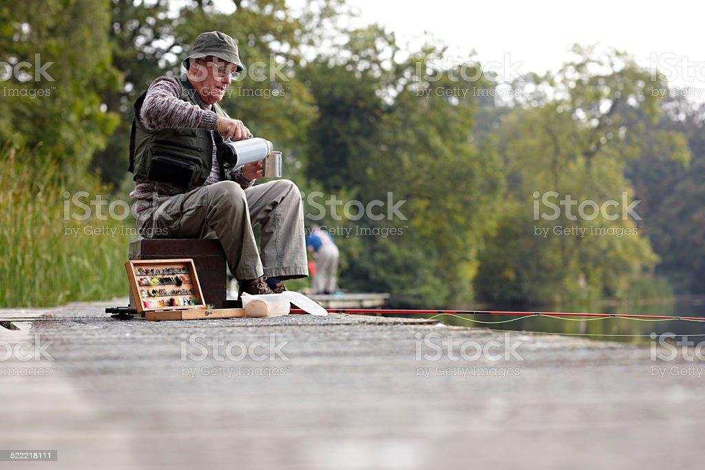 Senior fisherman having coffee on fishing dock stock photo
