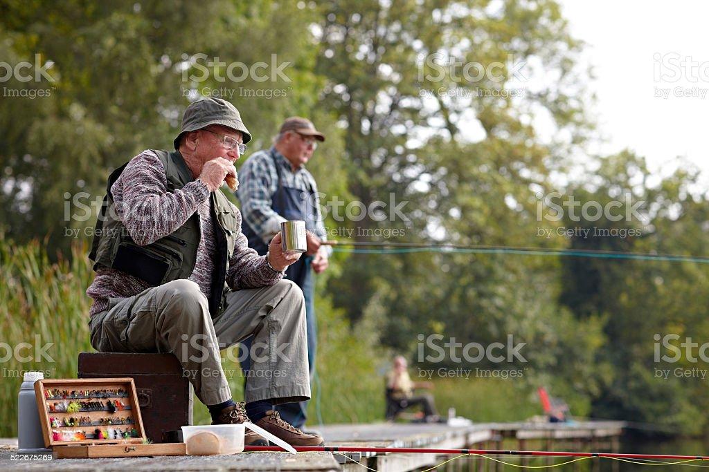 Senior fisherman having lunch stock photo