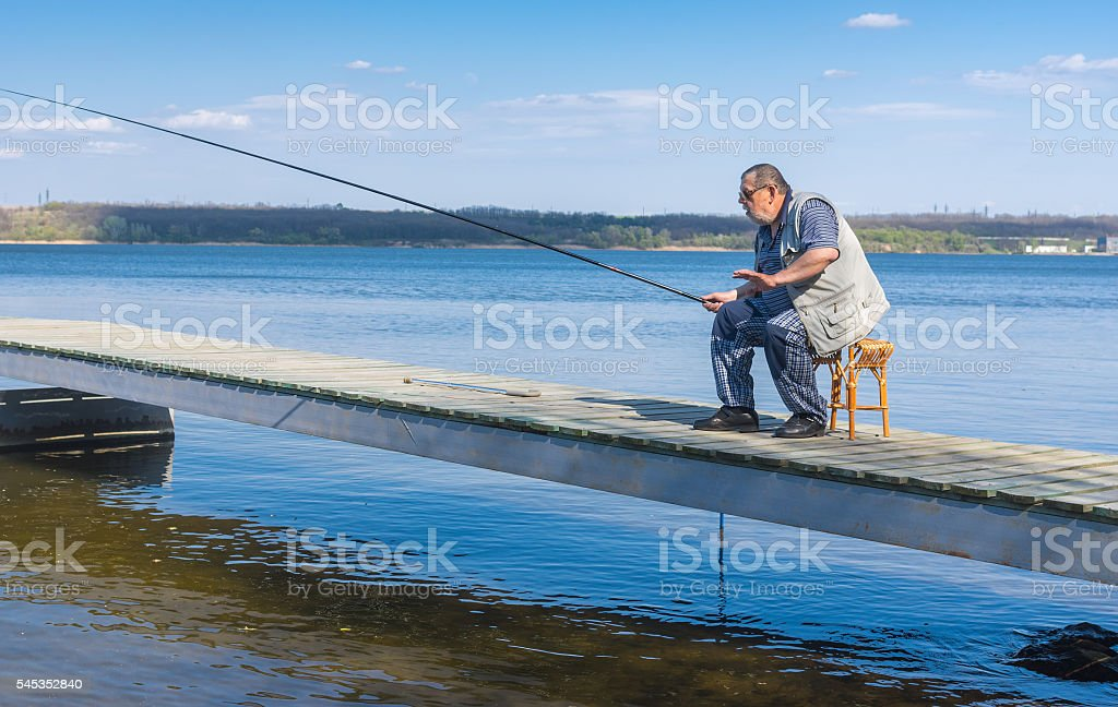 Senior fisherman sitting on a pier stock photo