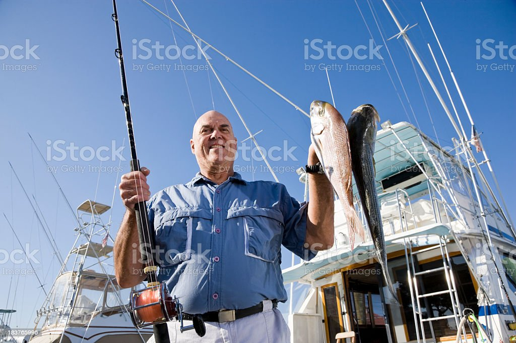 Senior fisherman with rod and fresh catch royalty-free stock photo