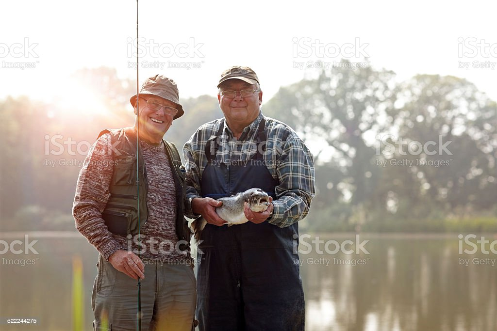 Senior fishermen with rod and fresh catch stock photo