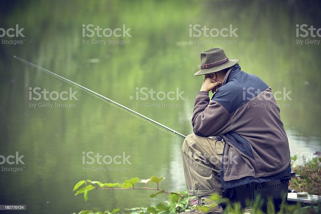 Senior fishing in peaceful natural surroundings royalty-free stock photo