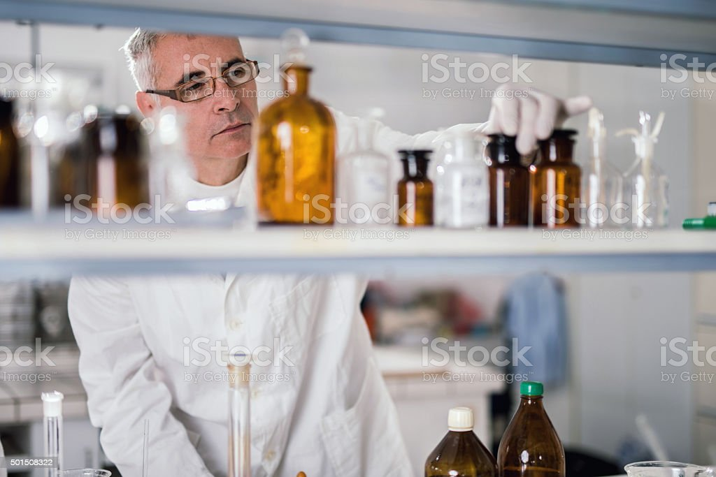 Senior forensic scientist choosing substances for his medical research. stock photo