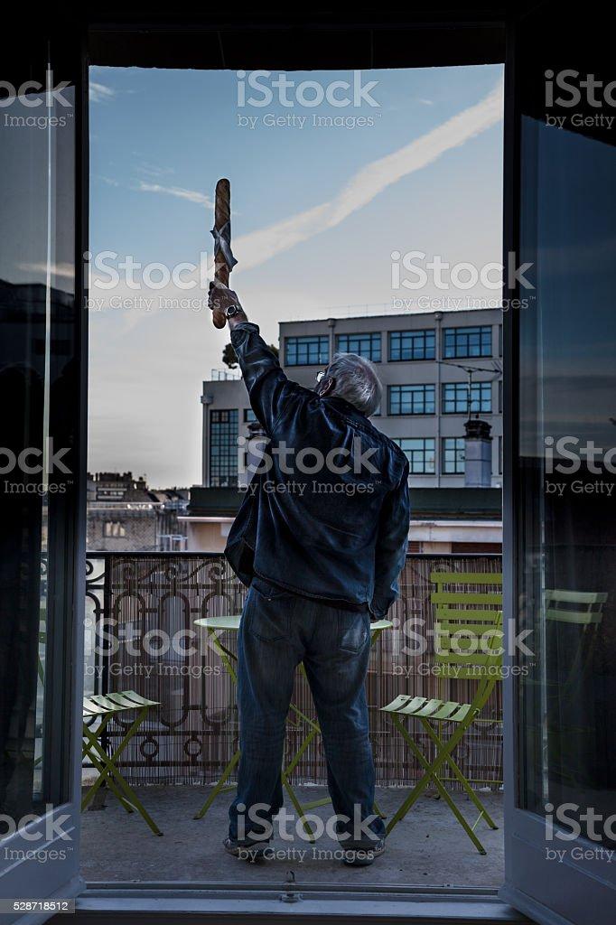 senior frenchman has fun raising baguette in stylish apartment stock photo