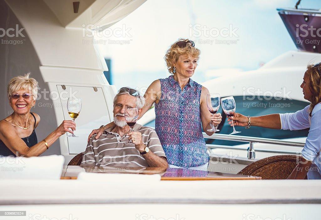 Senior friends enjoying on the sailing boat stock photo