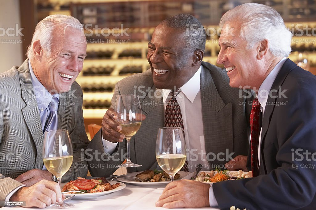 Senior friends in business suits having dinner royalty-free stock photo