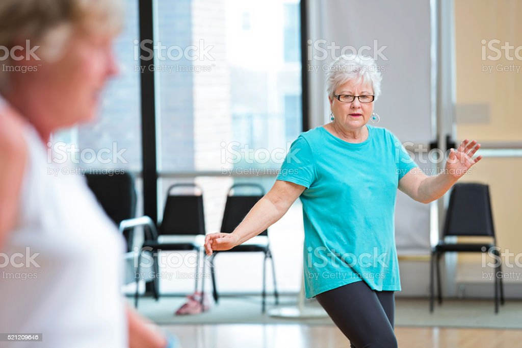 Pretty senior woman practices a new dance move in her exercise class....