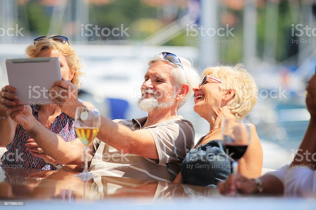 Senior friends making selfie with digital tablet stock photo