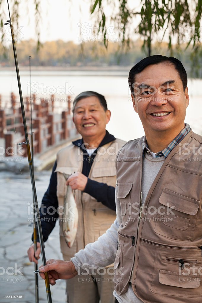 Senior friends portrait while fishing at a lake stock photo