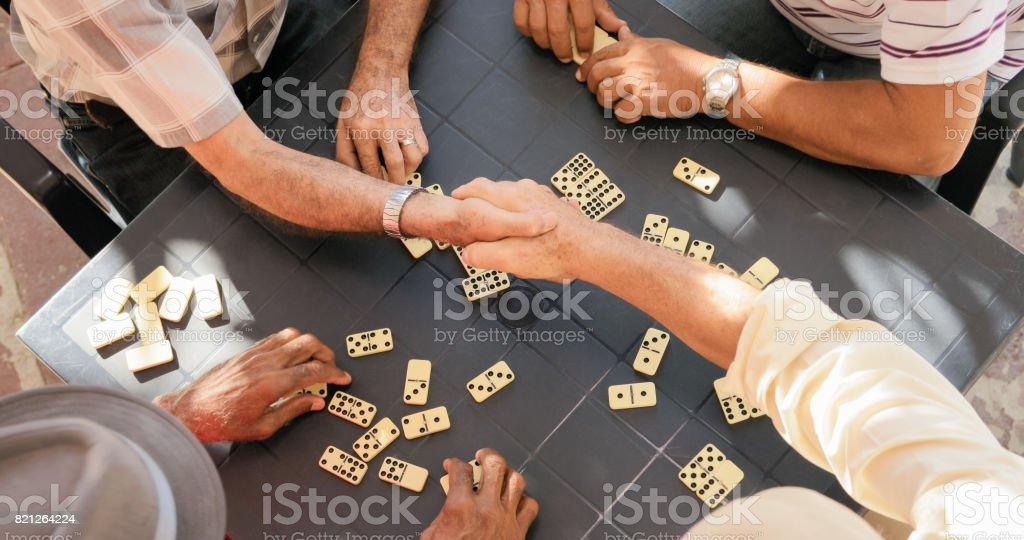 Senior Friends Shaking Hands Winning Game Of Domino stock photo