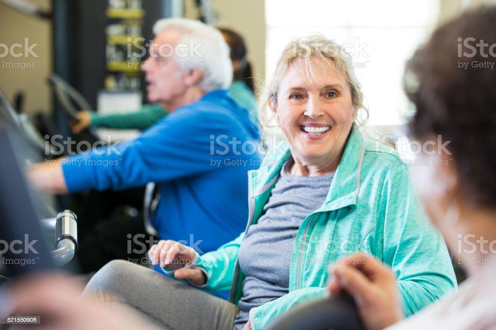 Senior friends visit while exercising at senior center stock photo