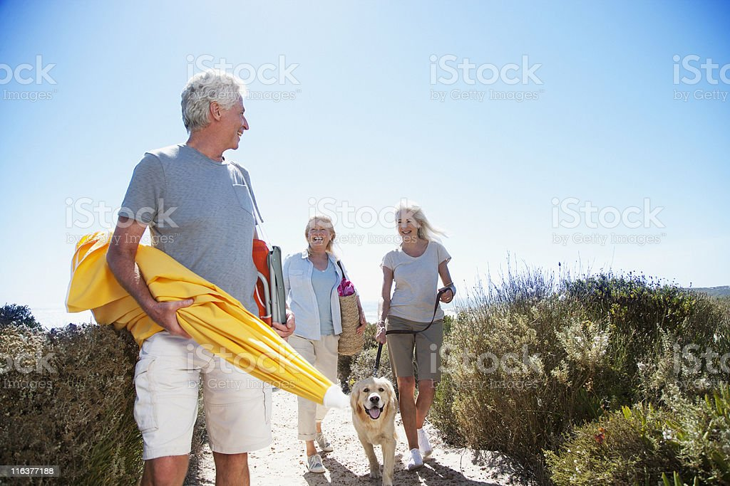 Senior friends with dog walking on beach path royalty-free stock photo