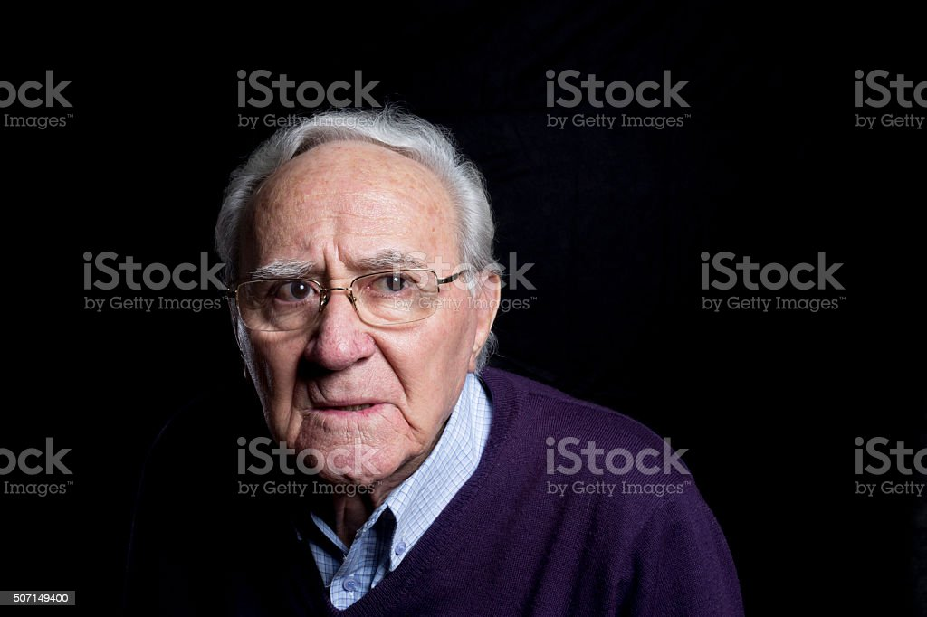 senior frowing portrait with glasses stock photo