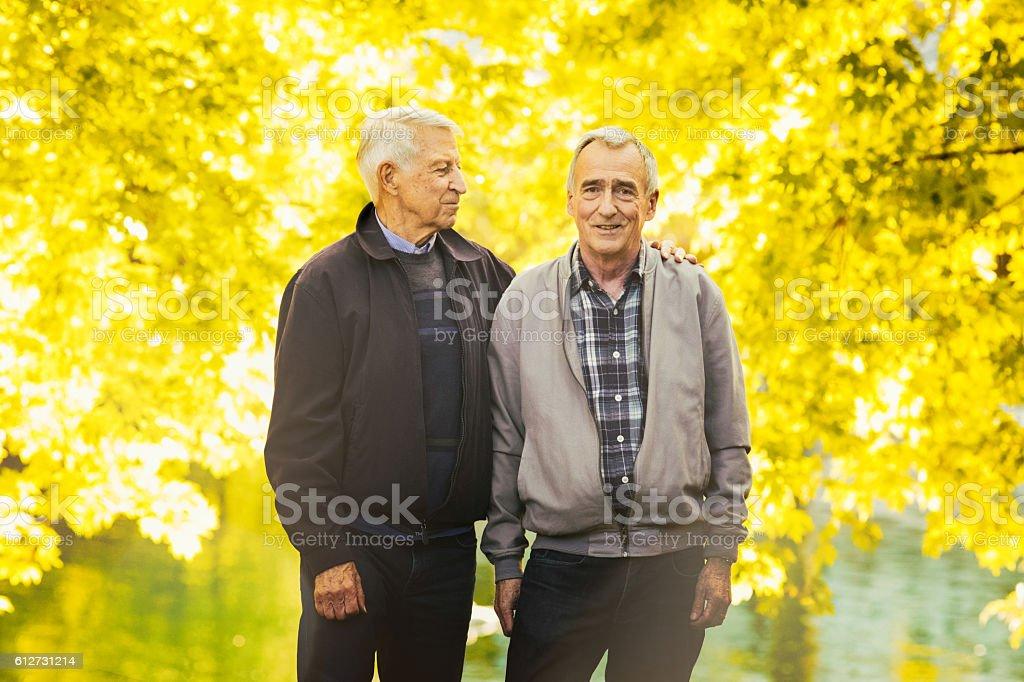 Senior gay couple Autumn portrait in park stock photo