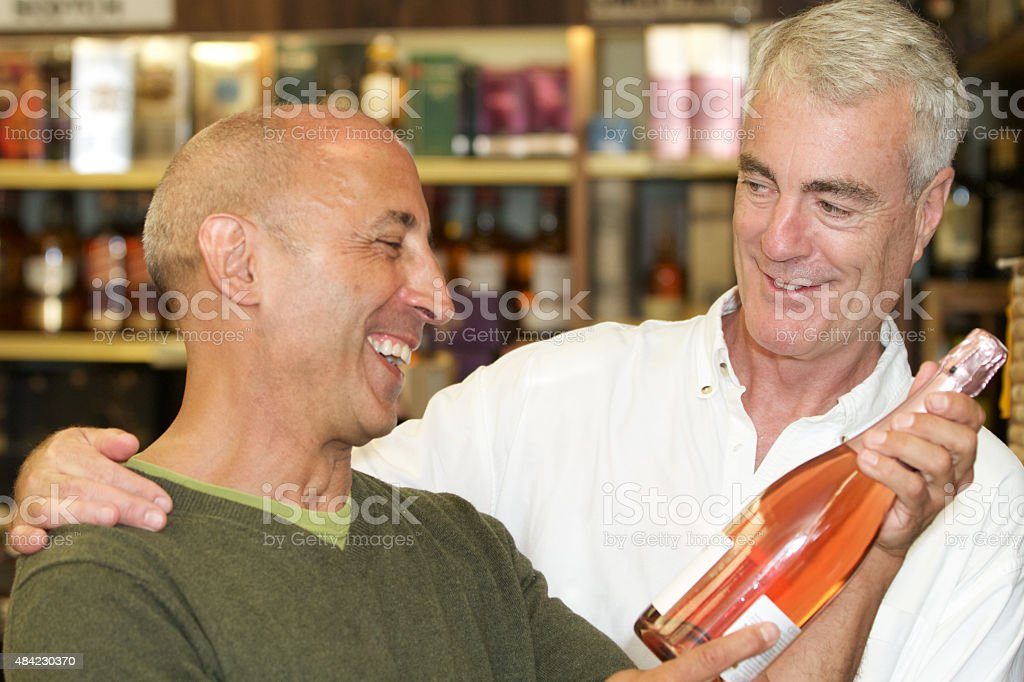 Senior Gay Male Couple Buying Champagne stock photo