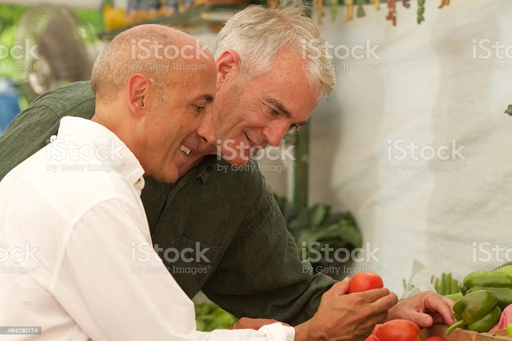 Senior Gay Male Couple Buying Produce at Farm Stand stock photo