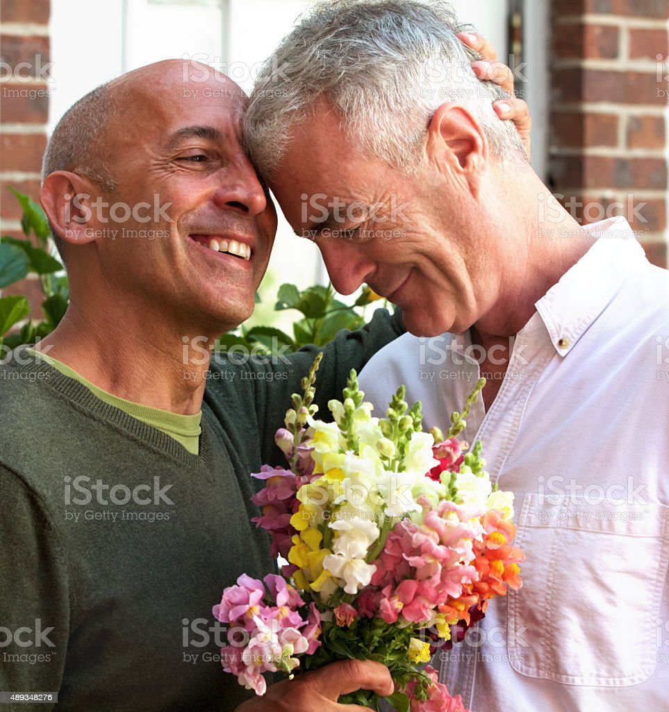Senior Gay Male Couple Celebrating with Bouquet of Flowers stock photo