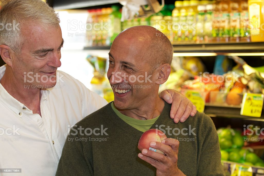 Senior Gay Male Couple Smiling and Shopping for Groceries stock photo