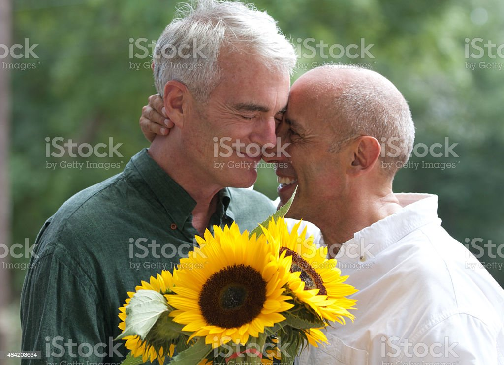 Senior Gay Male Couple with Sunflowers at Flower Stand stock photo