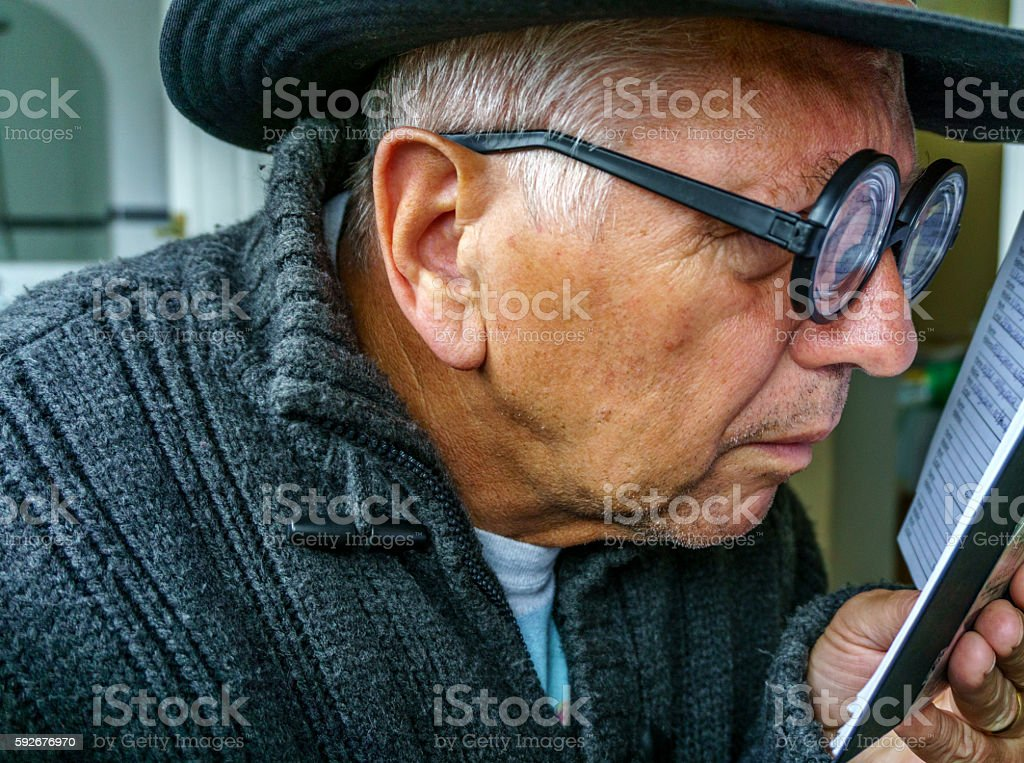 Senior geek wearing thick glasses reading address book stock photo