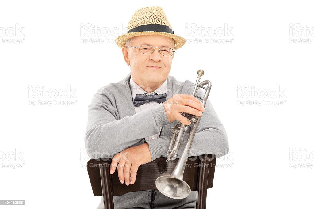 Senior gentleman holding trumpet seated on chair royalty-free stock photo