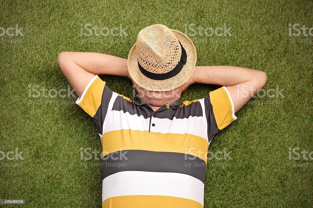 Senior gentleman lying in a field on green grass stock photo