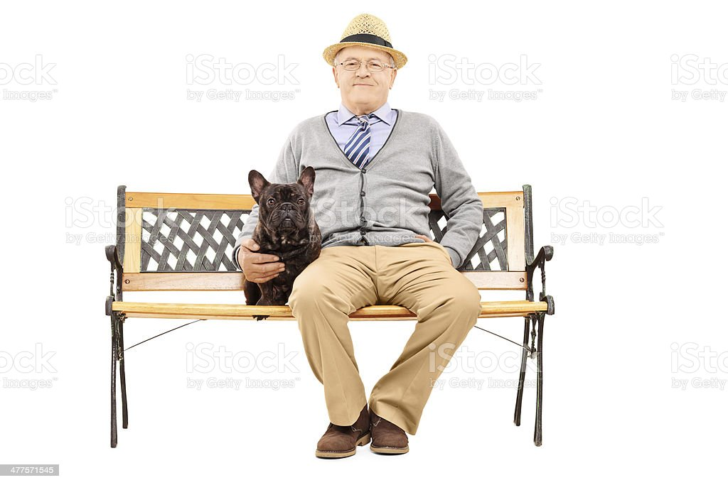 Senior gentleman seated on a bench with his dog royalty-free stock photo