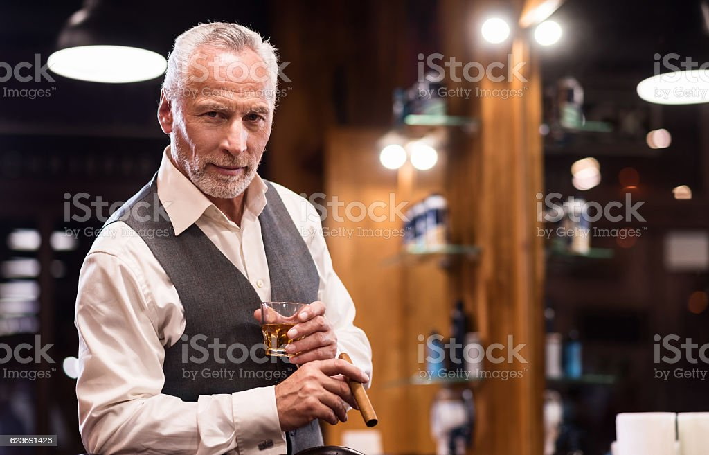 Senior gentleman with glass and cigar stock photo