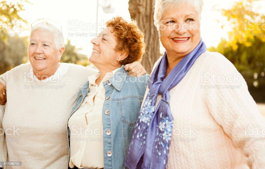 Senior girlfriends having fun in the park stock photo