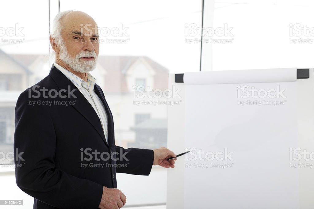 Senior giving presentation on a flip chart. royalty-free stock photo